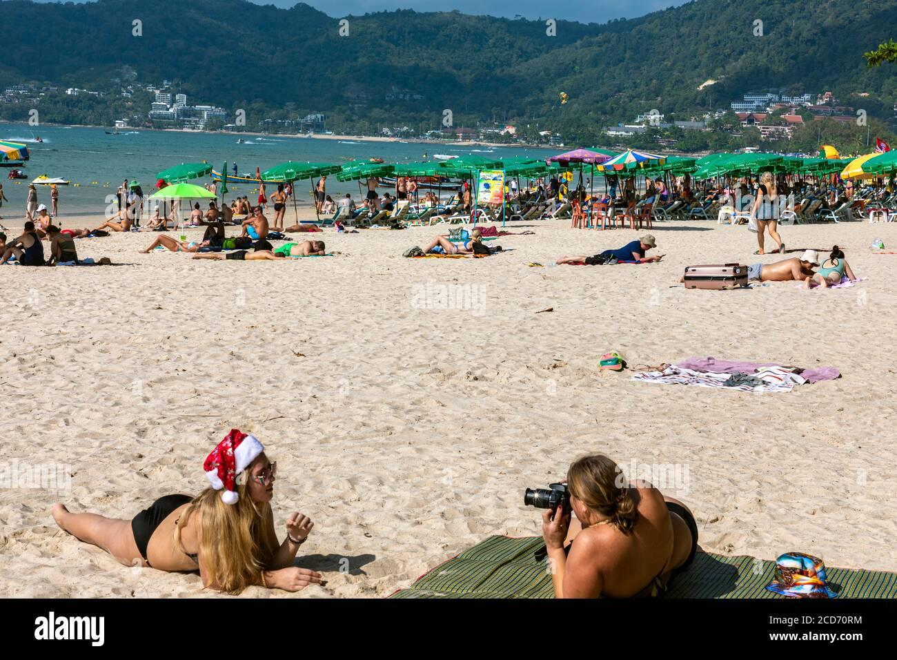Touristes prenant des photos à Santa Hat sur la plage à Noël, Patong, Phuket, Thaïlande Banque D'Images