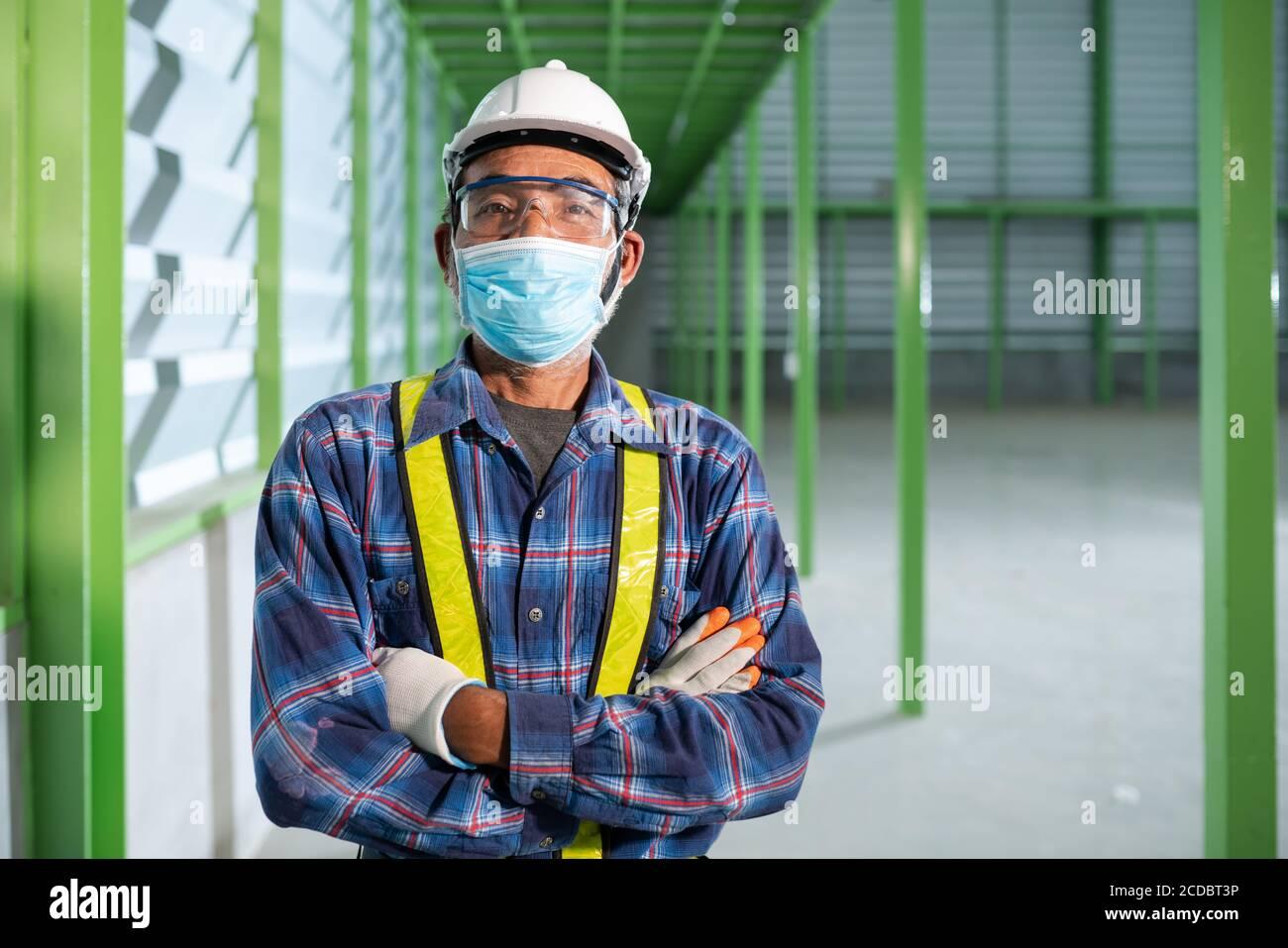 Ingénieur senior portant un masque pour travailler une nouvelle norme Banque D'Images