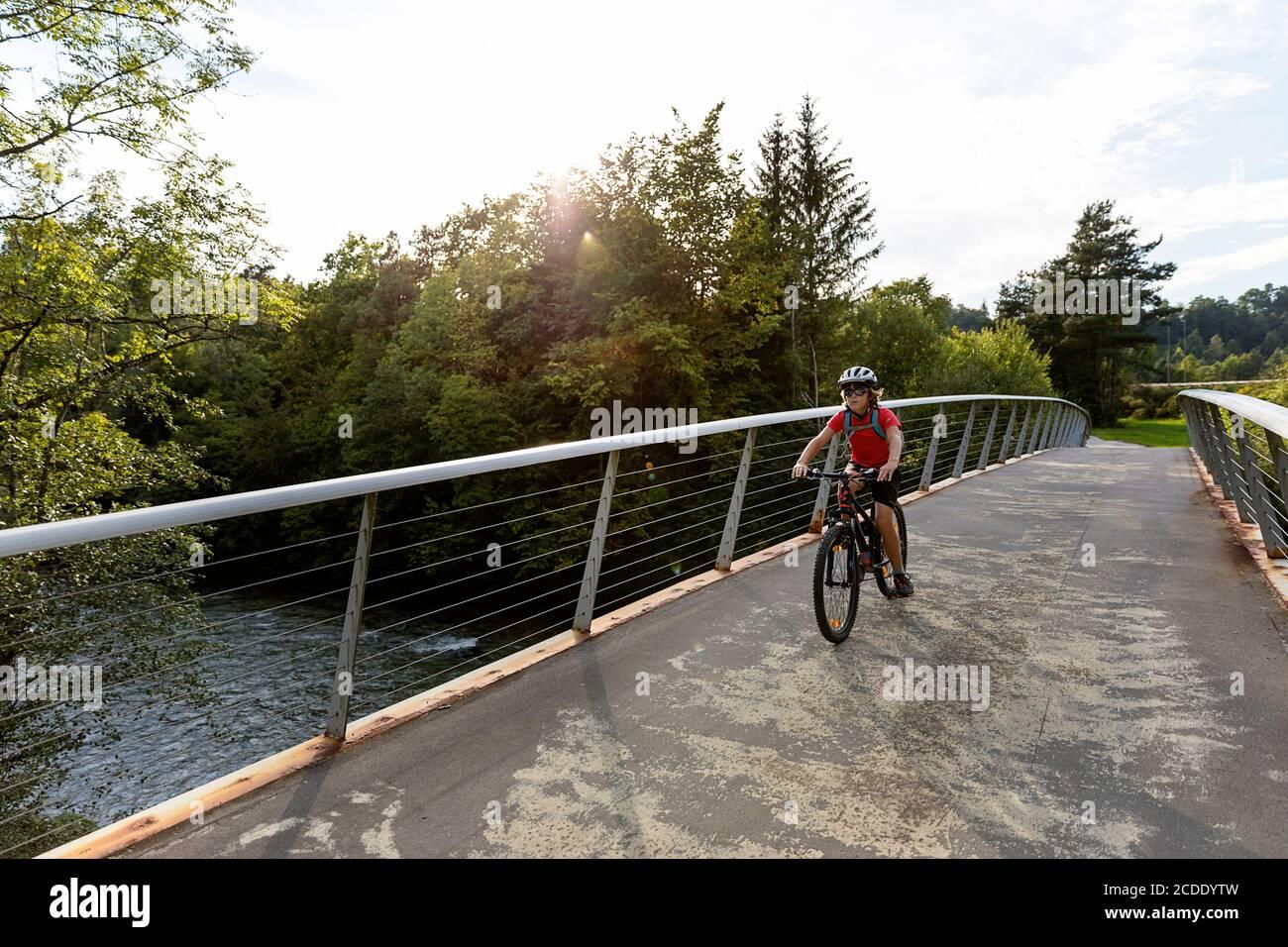 Un jeune garçon fait du vélo sur une passerelle Banque D'Images