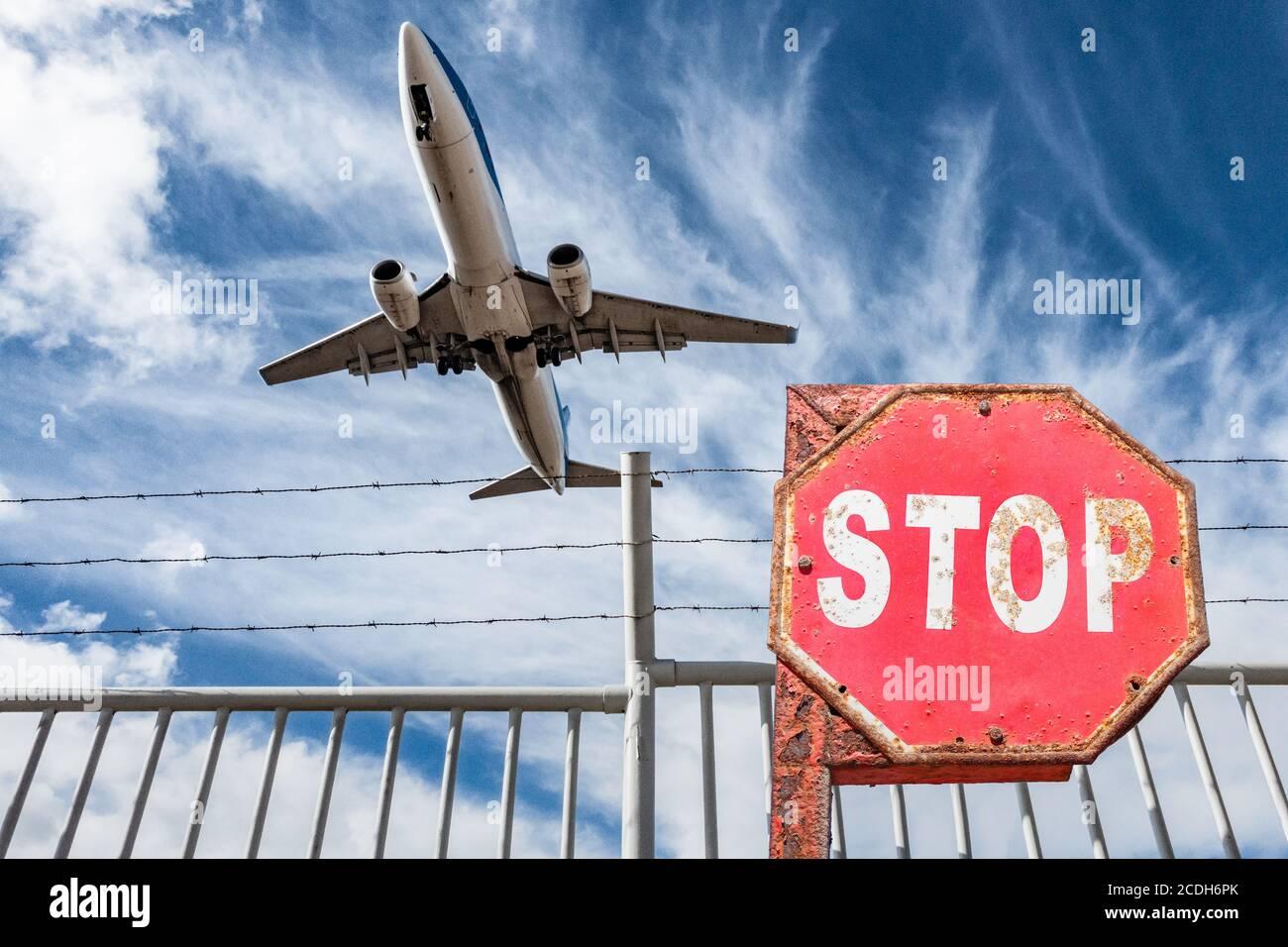 Avion survolant la clôture périphérique de l'aéroport avec le panneau stop en premier plan. Industrie aéronautique, Covid 19, coronavirus, tourisme..., concept. Banque D'Images