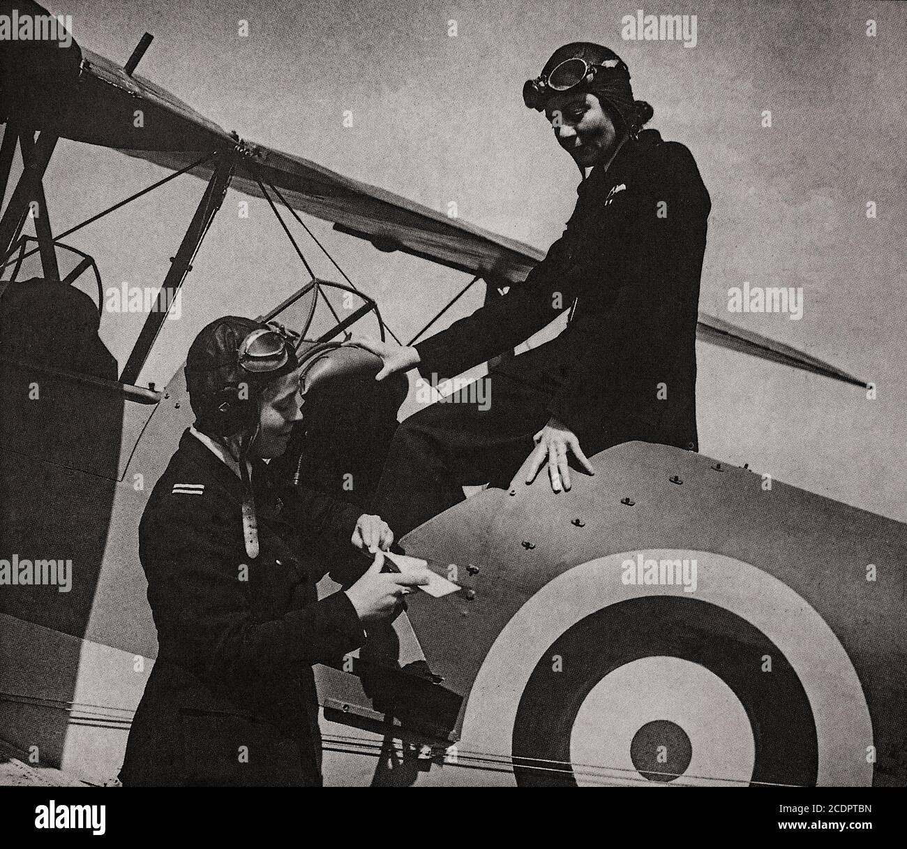Mme Gabriel Patterson (à gauche) instructeur en conversation avec Mme Grace Brown qui a fait voler son Tiger Moth en France avec des fournitures médicales pendant l'avance allemande de 1940. Les deux étaient membres de l'auxiliaire du transport aérien (ATA) mis en place au cours de la Seconde Guerre mondiale pour acheminer des avions militaires neufs, réparés et endommagés entre des usines, des usines d'assemblage, des points de livraison transatlantiques, des unités de maintenance (MU) et des escadrons de service actif et des aérodromes. Ils ont également fait voler du personnel de service d'urgence d'un endroit à l'autre et ont effectué des travaux d'ambulance aérienne. Banque D'Images