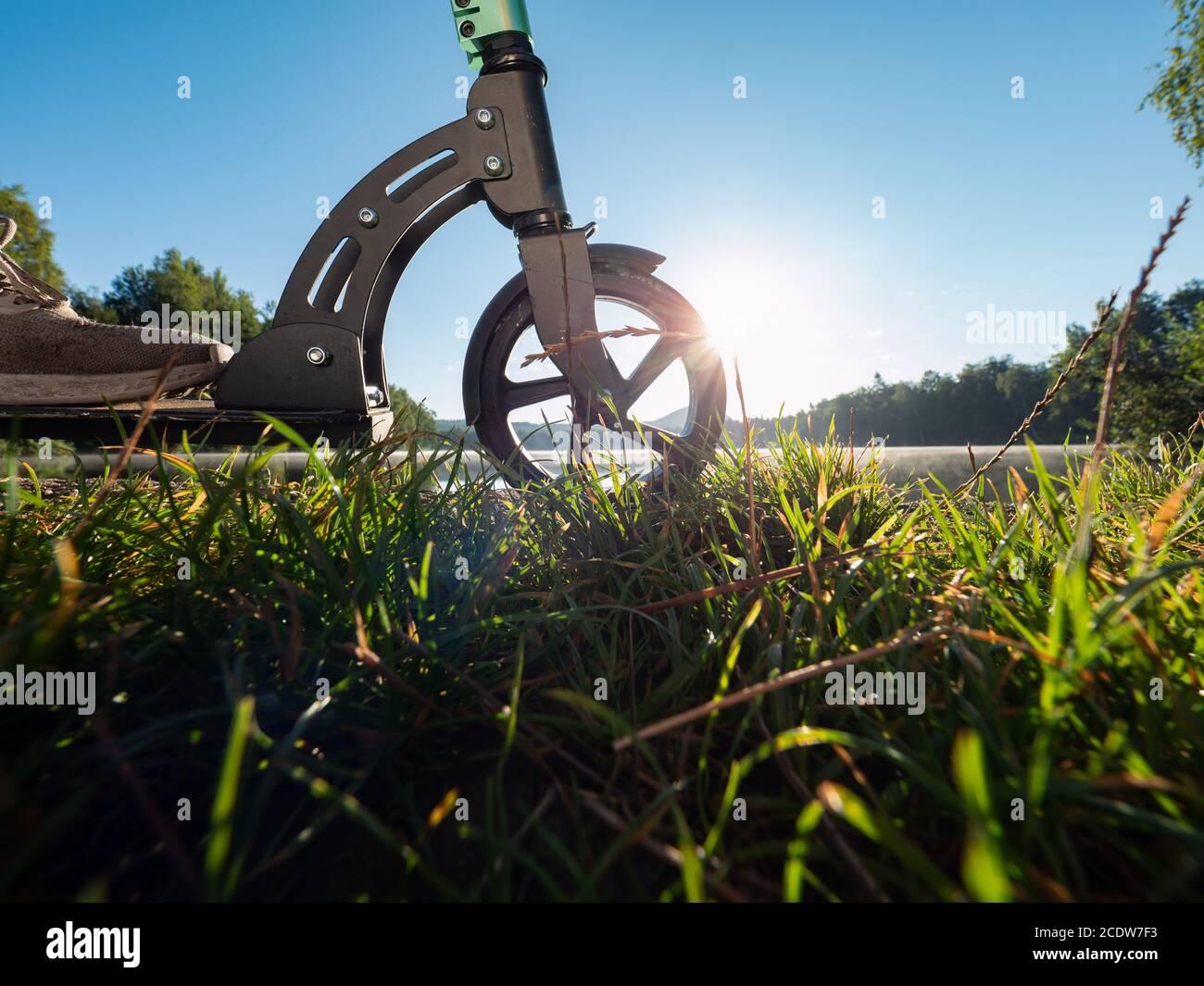 Gros plan du pneu de roue avant du scooter de poussée stationné au lac en soirée d'été. Fin de plaisir et rentrer à la maison au lit. Banque D'Images