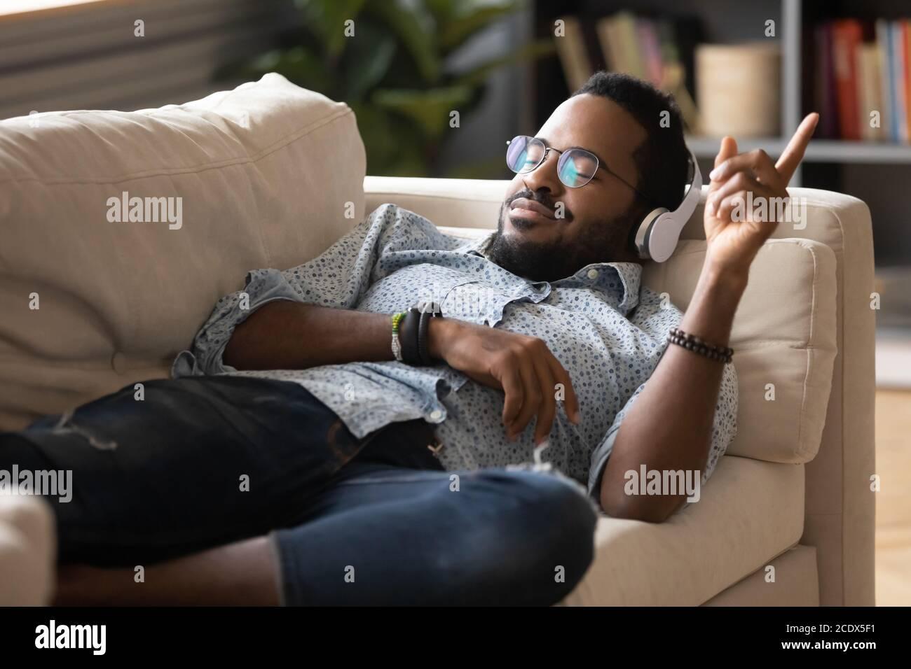 Homme afro-américain satisfait positif allongé sur un canapé, en appréciant la musique Banque D'Images