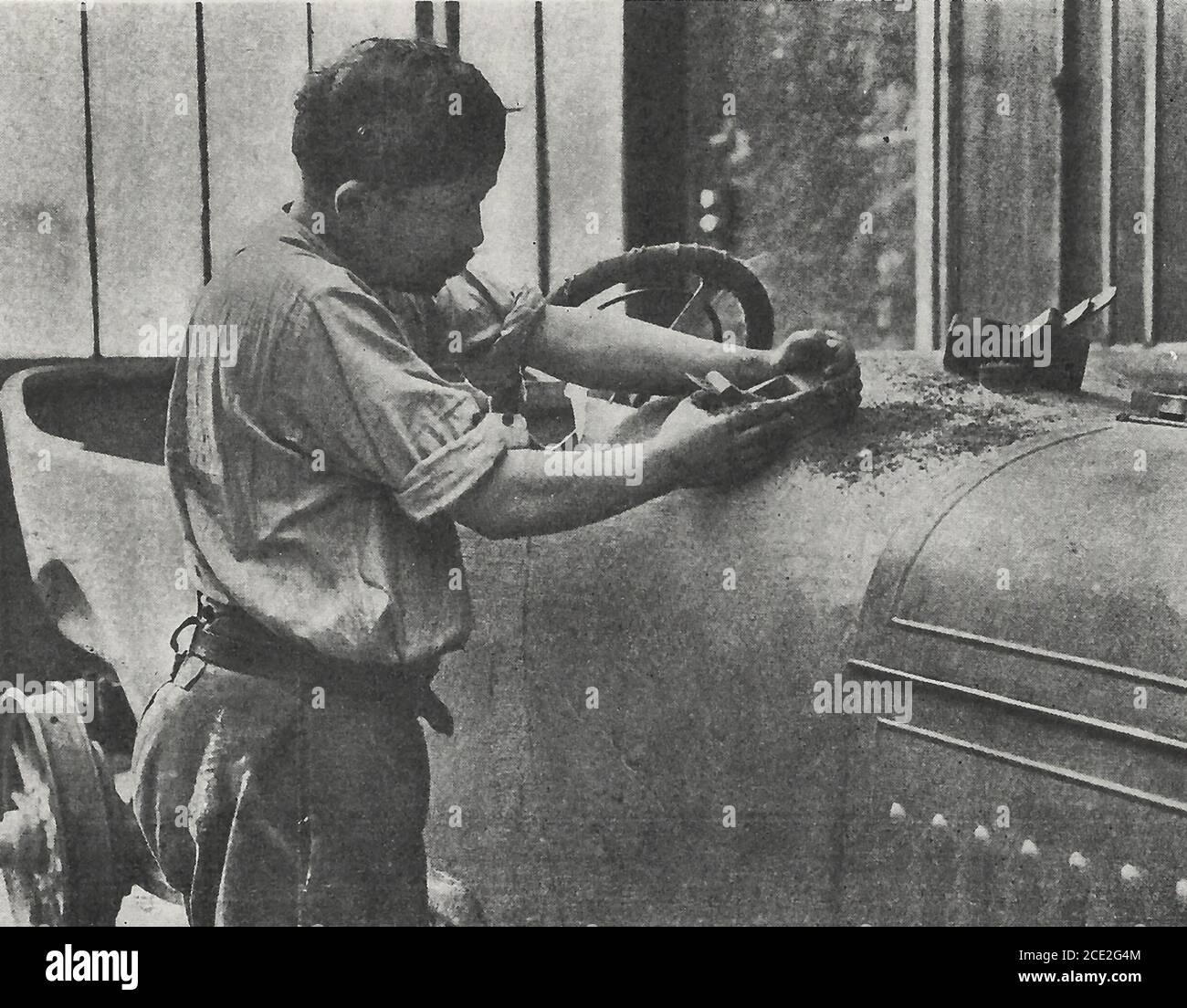Lissage de la carrosserie d'une voiture avec un plan avant application de peinture et de polissage - Fabrication d'une automobile, 1914 Banque D'Images