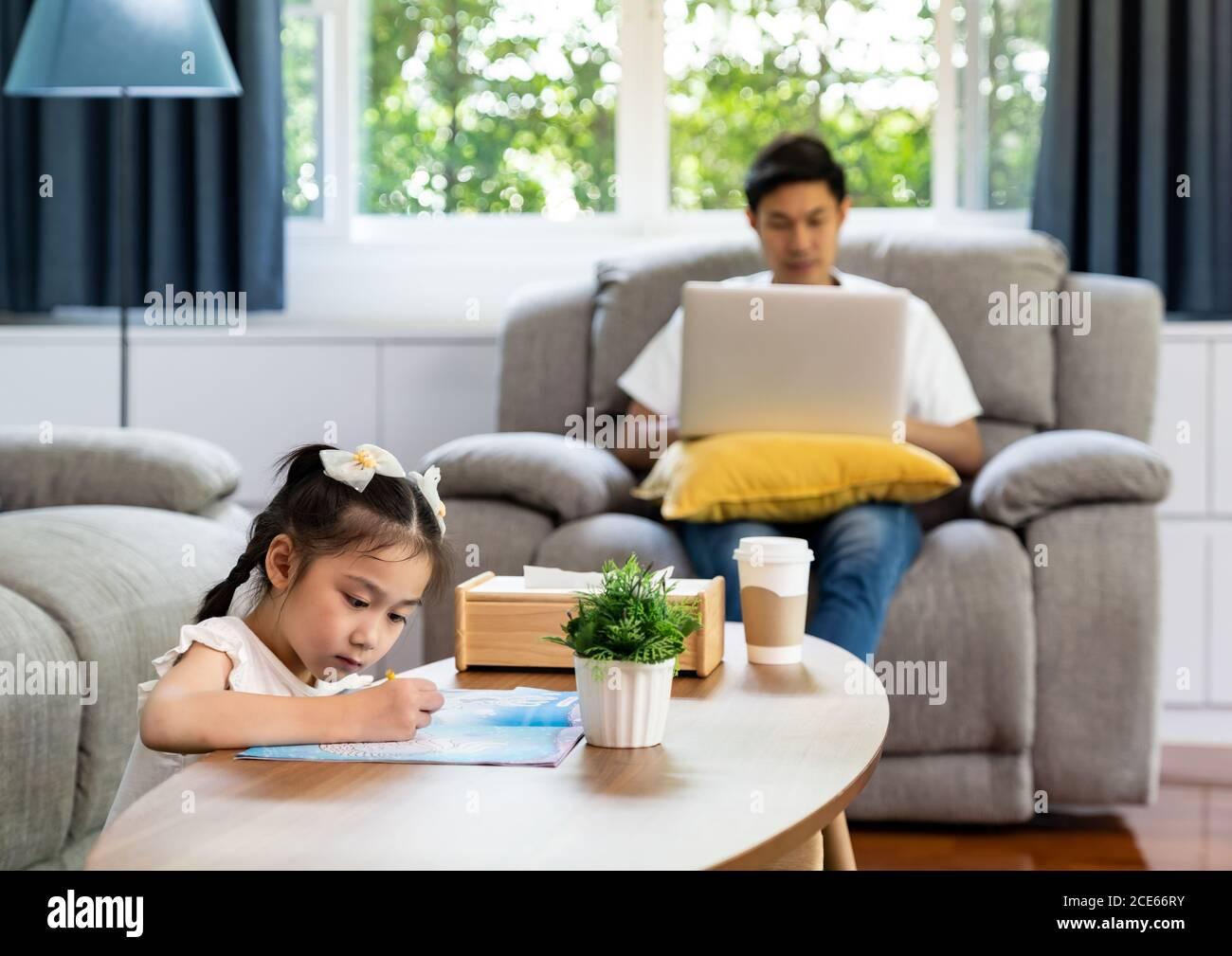 Fille dessin avec papa travaillant à la maison Banque D'Images