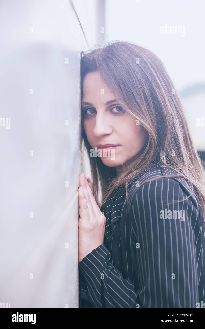 Belle femme penchée contre le mur Banque D'Images