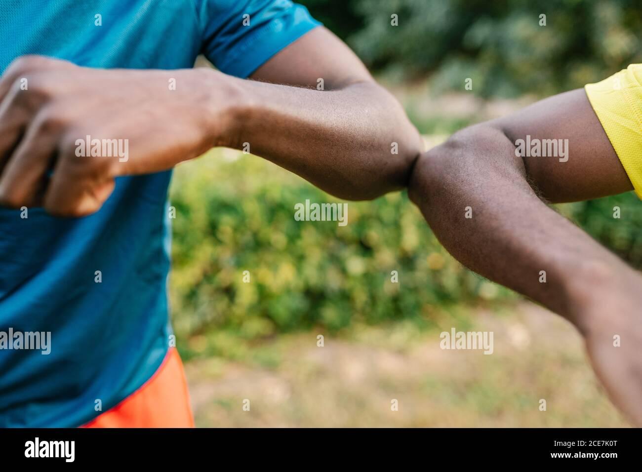 Gros plan de deux hommes noirs anonymes qui font la bosse du coude plein air dans le parc Banque D'Images