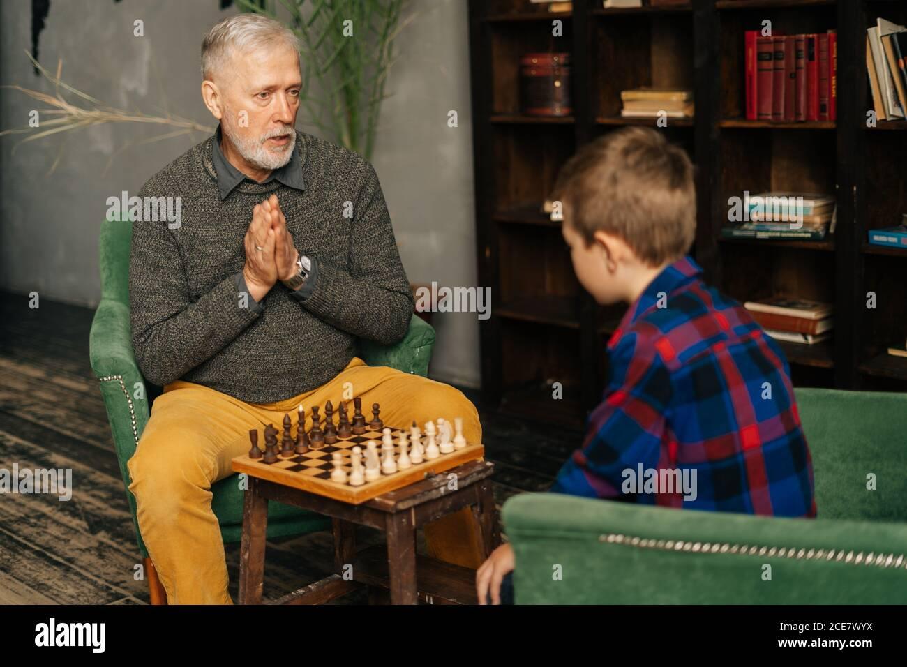 Grand-père adulte mature et ciblé expliquant les règles du jeu d'échecs au petit-enfant à la maison. Banque D'Images