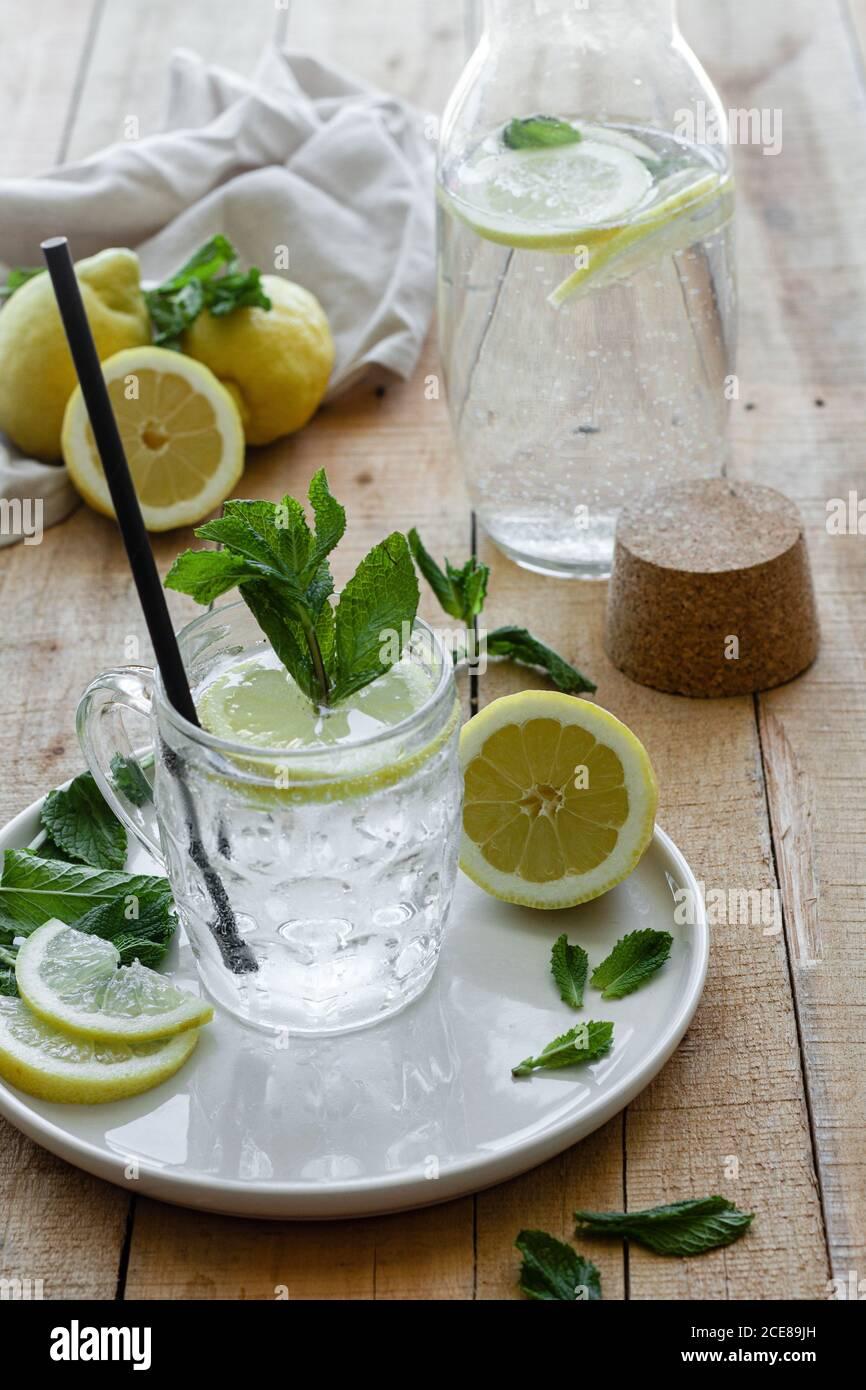 Boisson rafraîchissante froide avec soda et citron garni feuilles de menthe fraîche servies sur une tasse en verre avec de la paille table en bois Banque D'Images