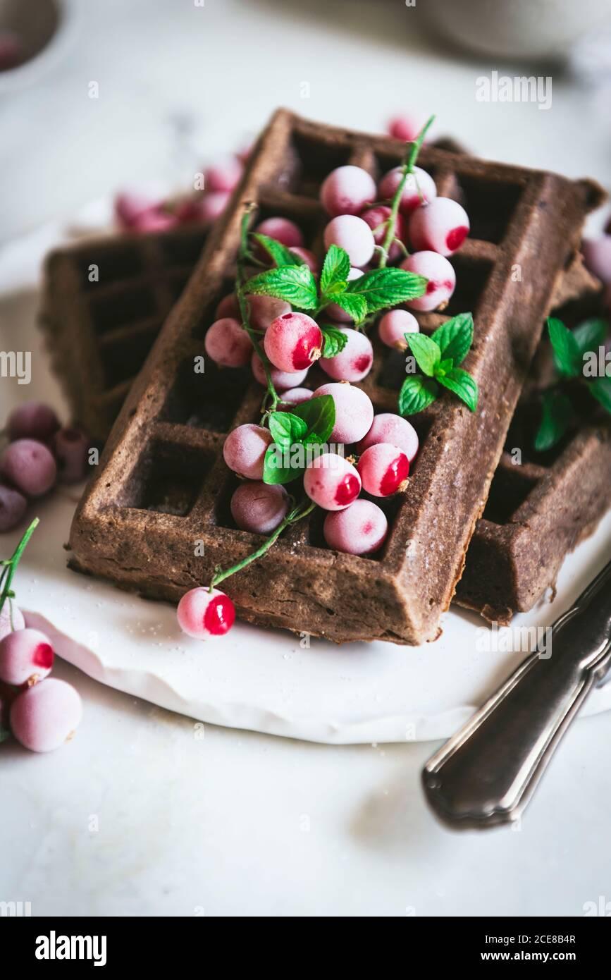 Des gaufres savoureuses au chocolat aux flocons d'avoine avec baies de gooseberries sont servies sur plaque blanche avec cuillère et couteau sur bois clair tableau Banque D'Images