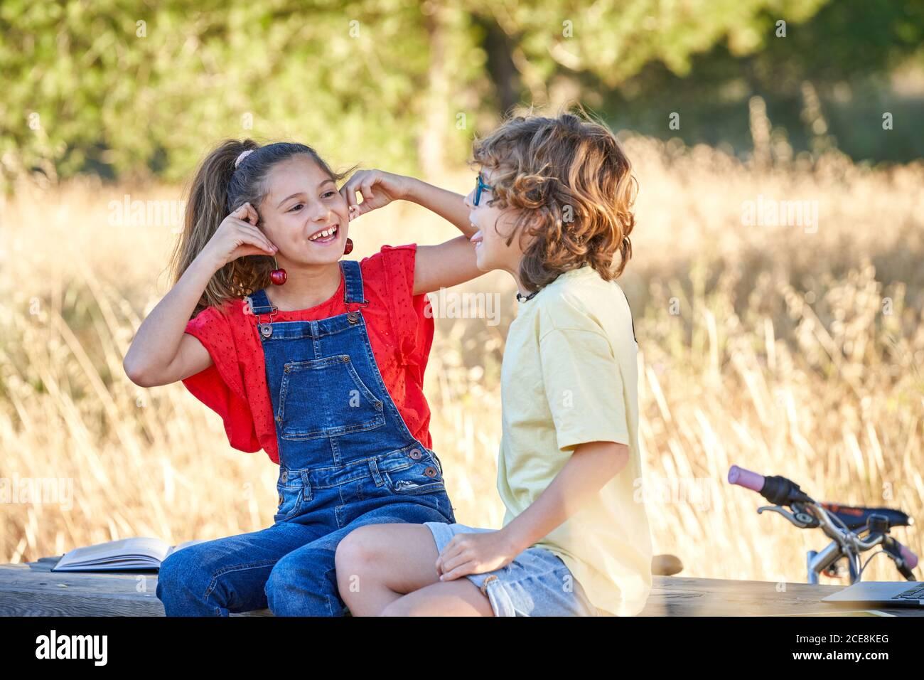 Un garçon et une fille de dix ans se grignoter sur une table en bois dans la campagne, avec des fruits, des sandwiches et de l'eau. Banque D'Images