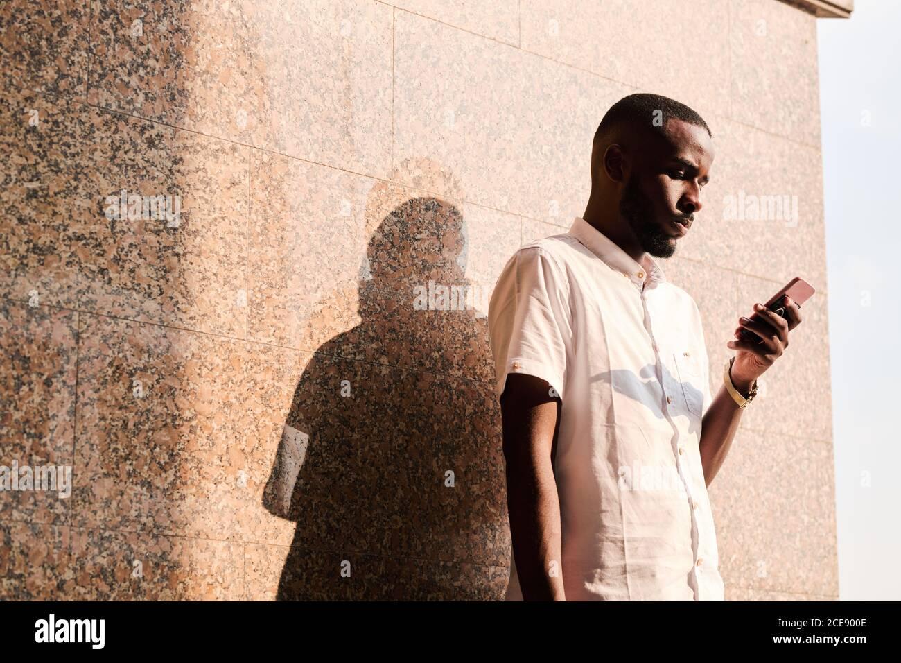Jeune homme noir concentré en chemise blanche debout au mur à l'extérieur et en lisant des sms sur le téléphone ou en vérifiant le courrier Banque D'Images