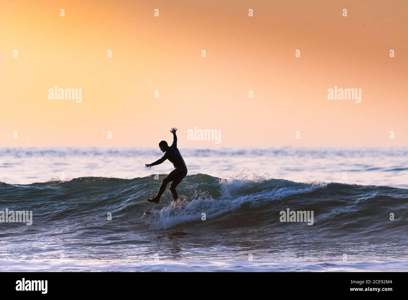 Un surfeur qui monte une vague et se tient sur une jambe en soirée à Fistral, à Newquay, en Cornwall. Banque D'Images