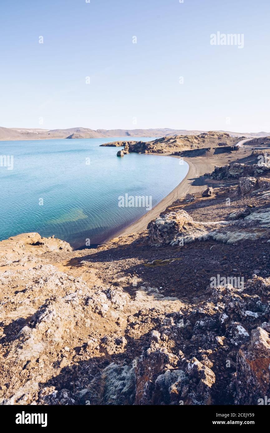 Rive en pierre d'une rivière large avec eau bleue entre les collines En Islande Banque D'Images