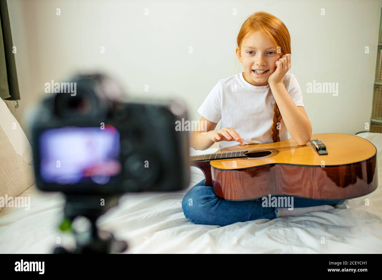 mignon adorable enfant blogueur jouer de la guitare, parler à la caméra comment elle a appris à jouer de la guitare acoustique, elle est autodidacte Banque D'Images