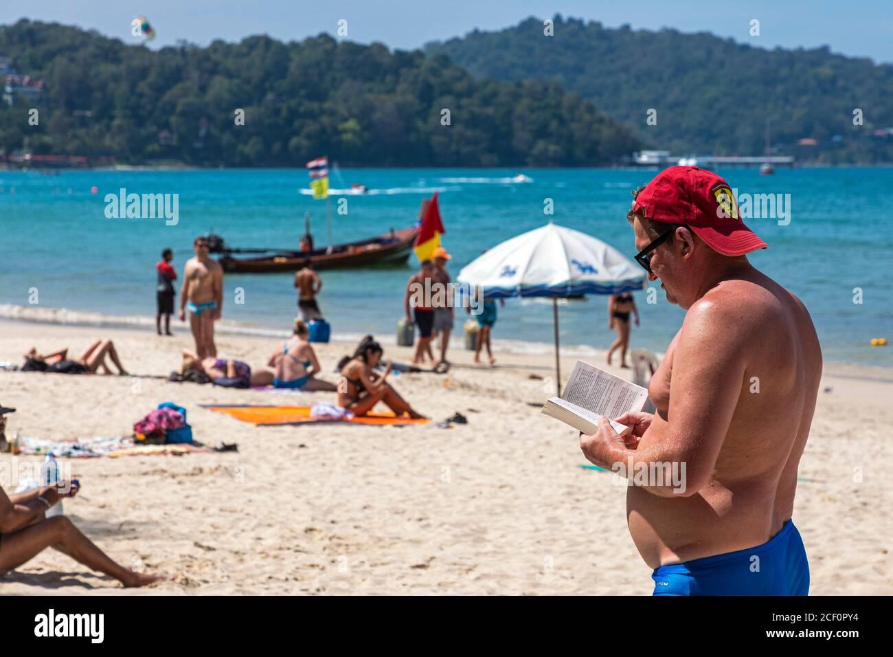 Touristes russes, lecture et bains de soleil se tenant sur la plage de Patong, Phuket, Thaïlande Banque D'Images