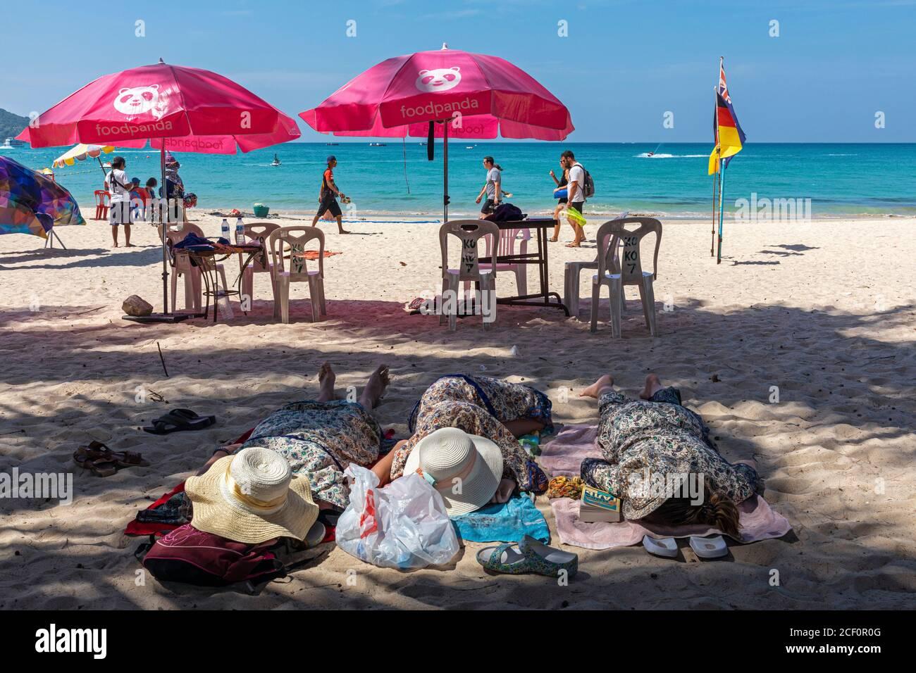 Touristes dormant sur le sable à Patong Beach, Phuket, Thaïlande Banque D'Images