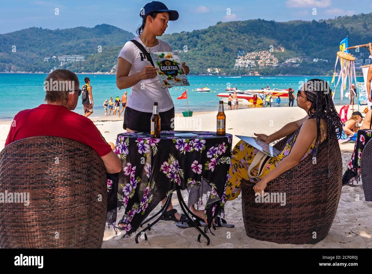 Serveuse et clients au bar de la plage, Patong, Phuket, Thaïlande Banque D'Images