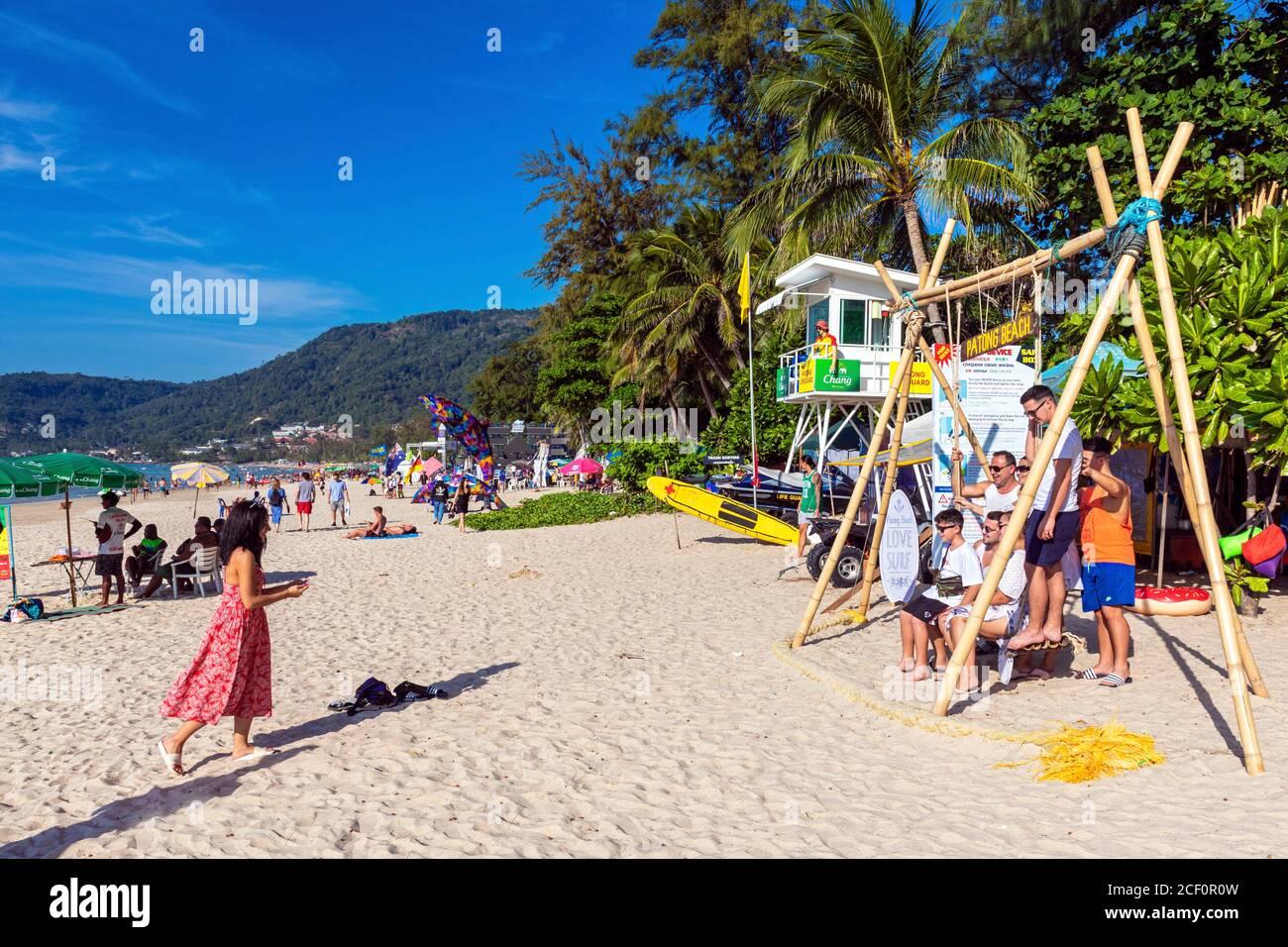 Famille touristique et balançoire en bois sur la plage de Patong, Phuket, Thaïlande Banque D'Images