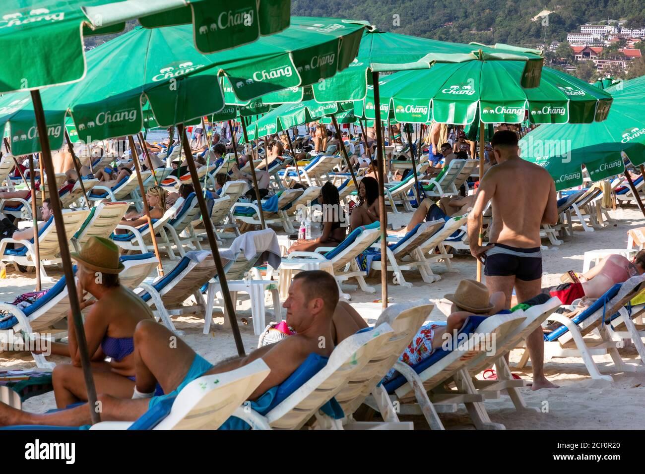 Les touristes utilisant des parasols et des chaises longues sur la plage de Patong, Phuket, Thaïlande Banque D'Images