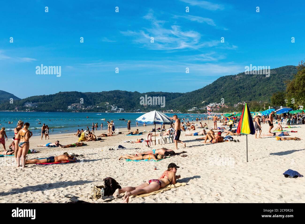 Touristes se bronzer sur la plage, Patong, Phuket, Thaïlande Banque D'Images