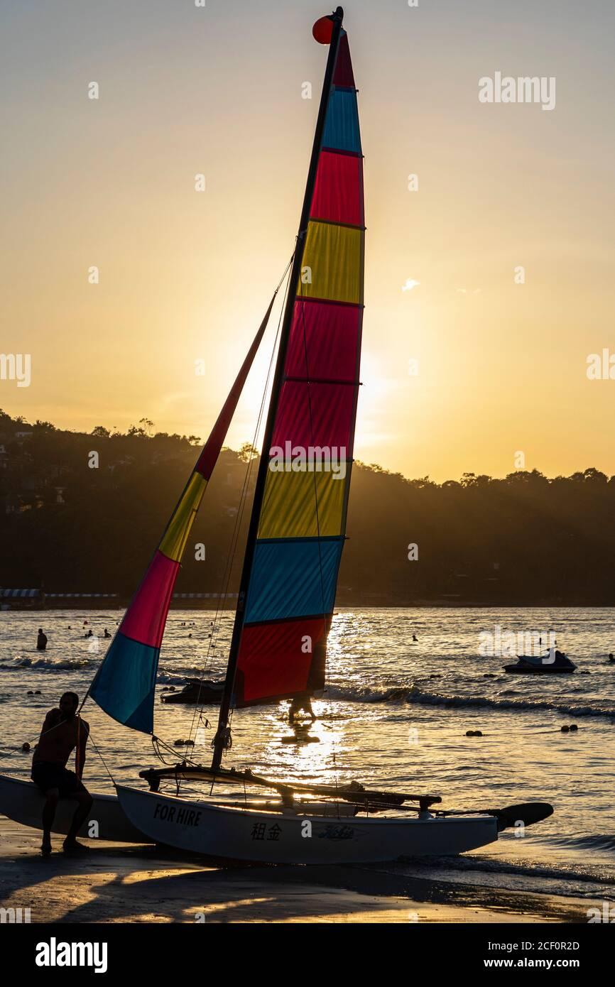 Location de bateau à voile sur la plage de Patong au coucher du soleil, Phuket, Thaïlande Banque D'Images