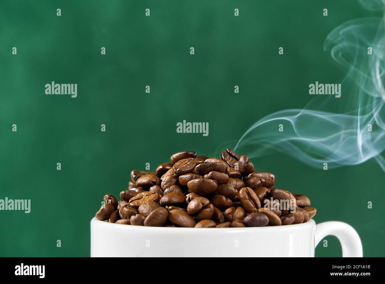 Concept de la journée internationale du café. Tasse de café blanc en gros plan pleine de grains de café sur fond vert avec fumée sur le dessus. Banque D'Images