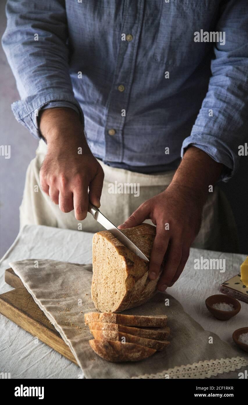 Homme en tranches de pain de levain maison frais Banque D'Images