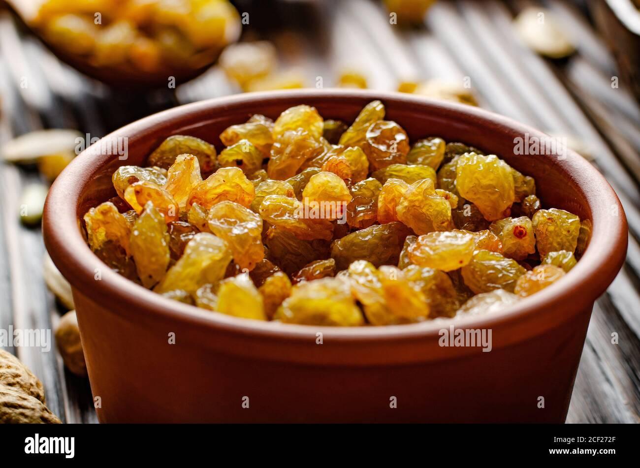 Raisins blancs dans un bol en argile sur une table de cuisine en bois fond de nourriture. Banque D'Images