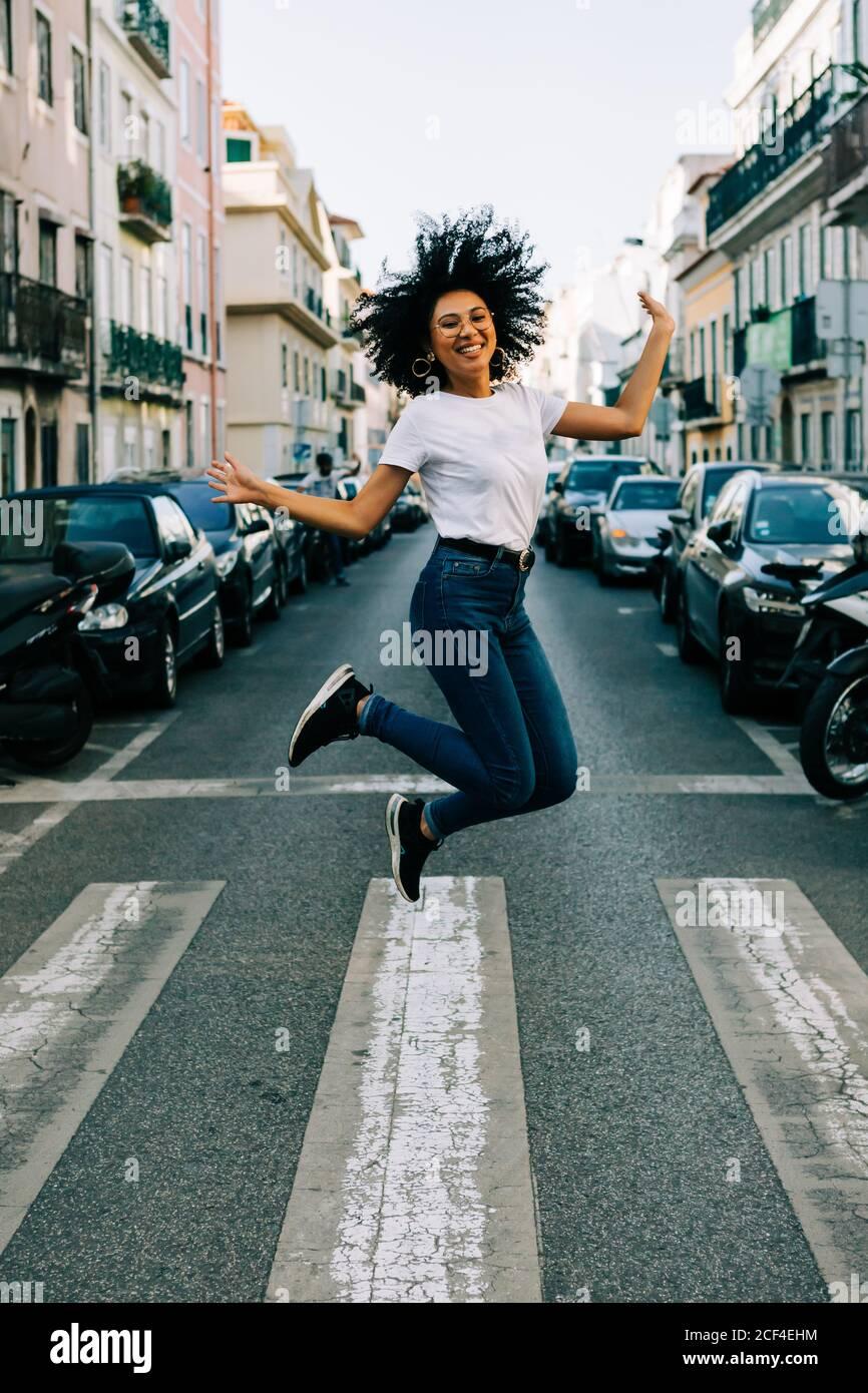 Jeune femme afro-américaine joyeuse en jeans et t-shirt blanc sauter pour la joie dans la rue de la ville le jour Banque D'Images