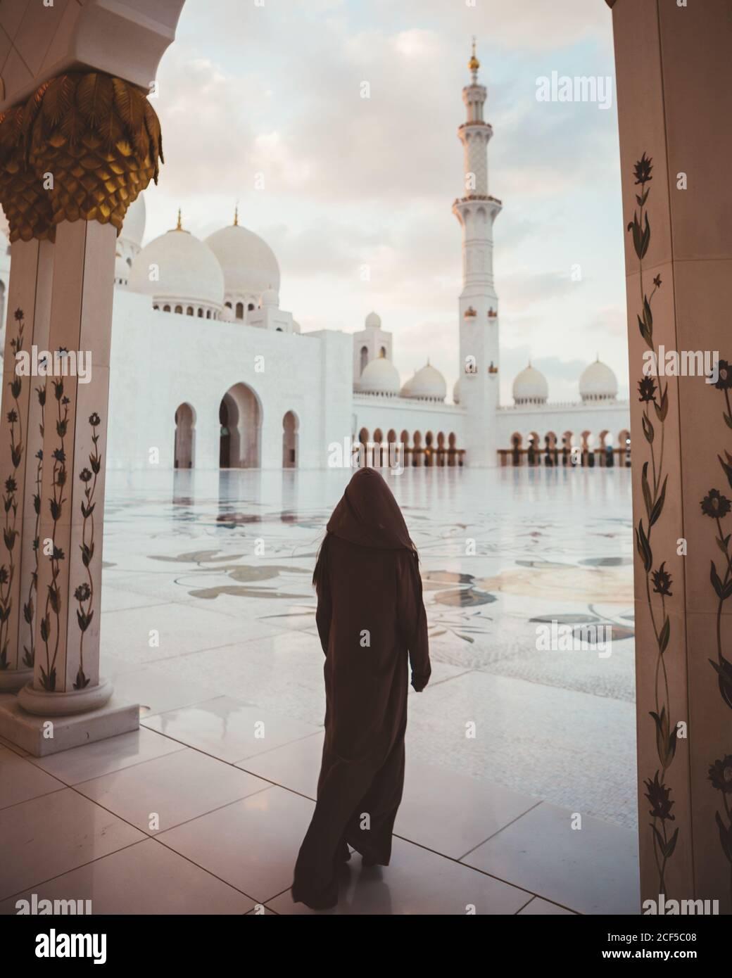 Vue arrière de la femme islamique anonyme en robe noire longue marchant sur la place carrelée de la majestueuse mosquée blanche, Dubaï Banque D'Images