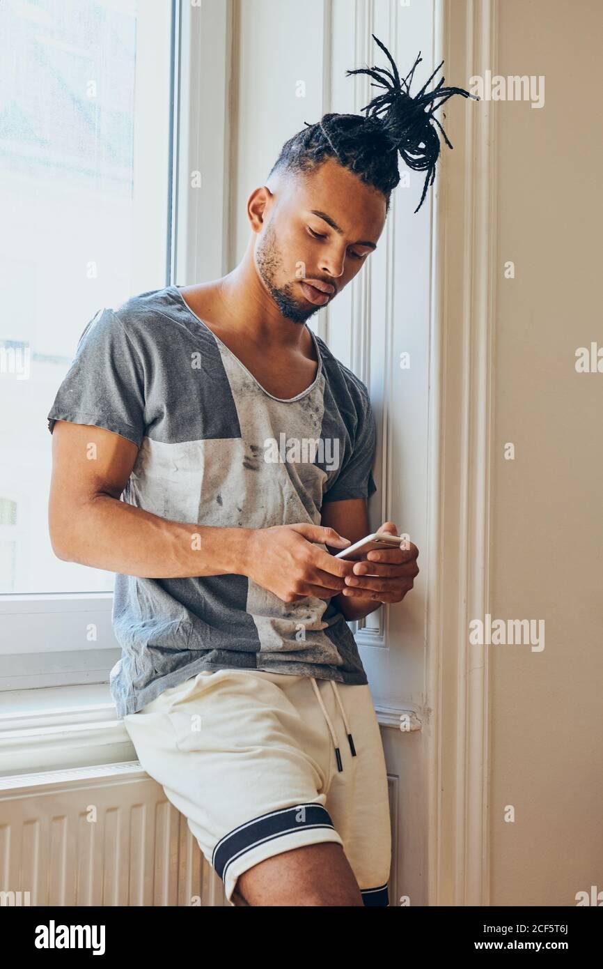 Jeune homme afro-américain avec une coiffure créative debout seuil de fenêtre et navigation dans le téléphone mobile Banque D'Images
