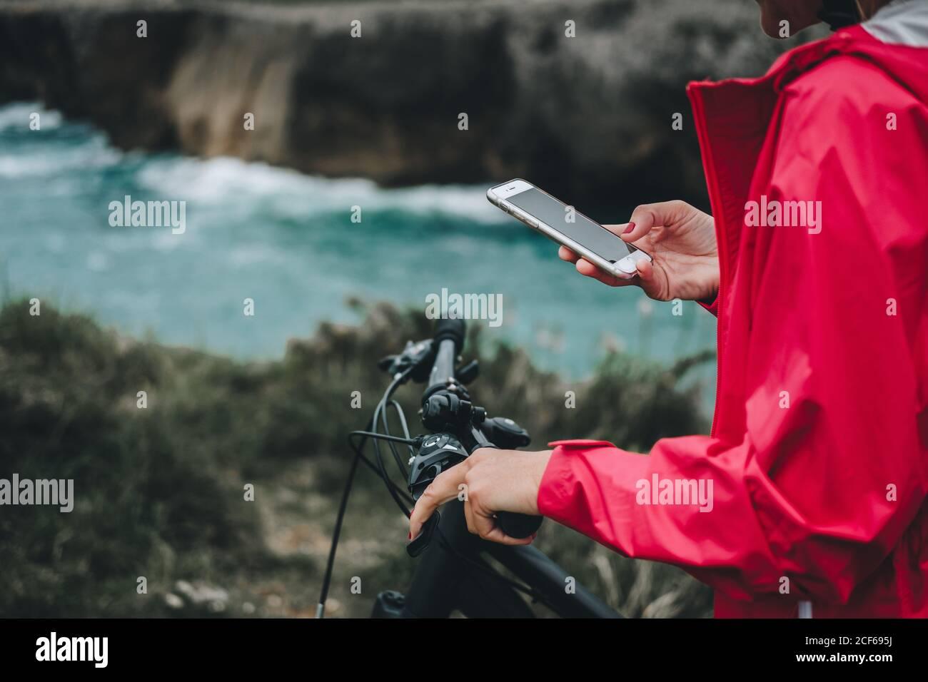 Vue rapprochée de la main d'une femme anonyme sur la navigation à vélo téléphone portable Banque D'Images