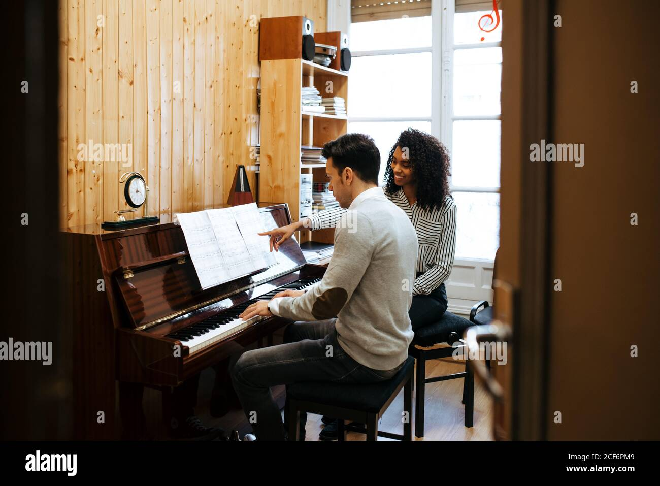 Jeune homme apprenant à jouer du piano près d'une femme noire enseignante en studio de musique Banque D'Images