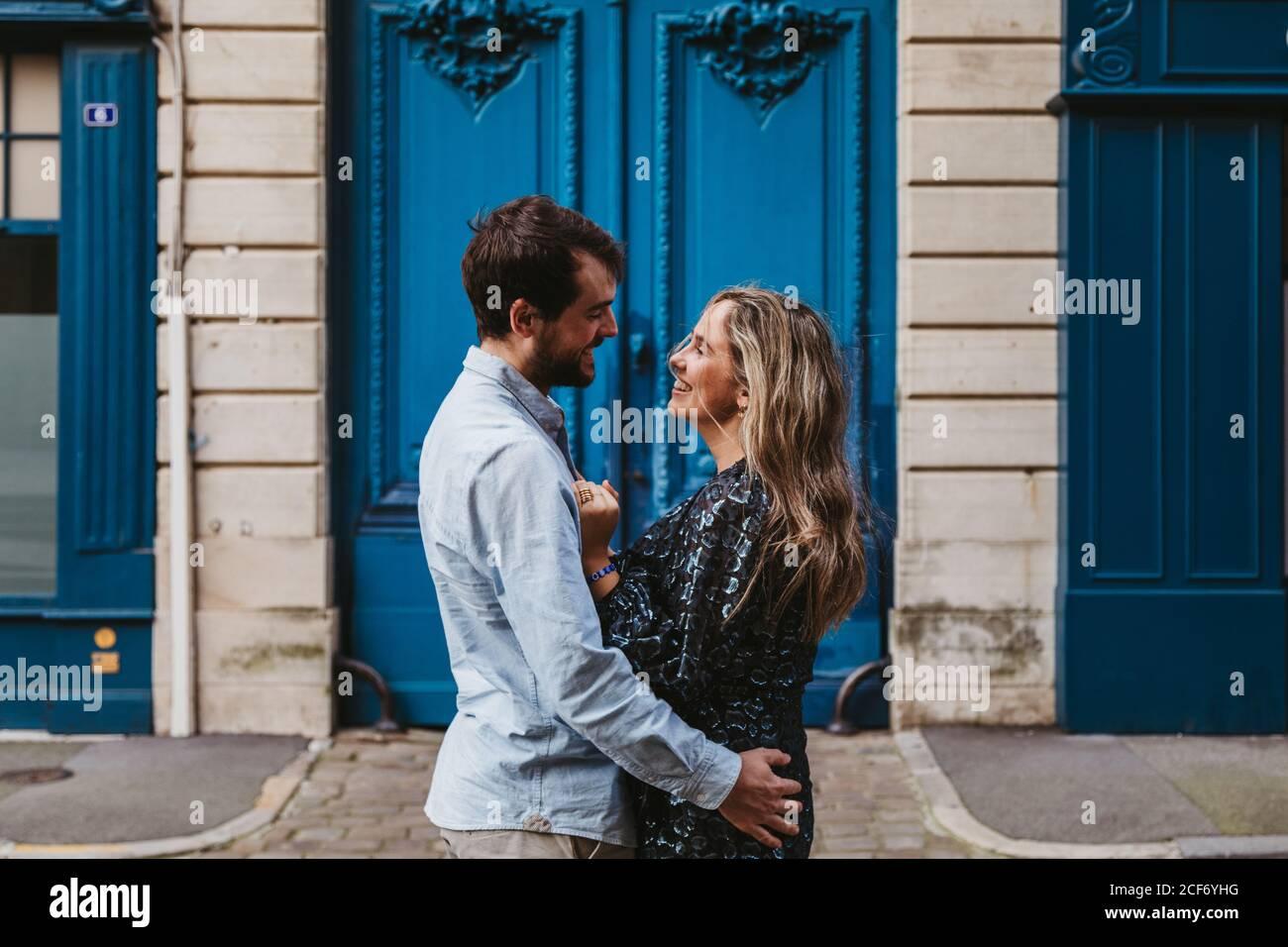 Vue latérale d'un jeune couple heureux dans des vêtements décontractés qui s'embrasent se regardant l'un contre l'autre en se tenant contre un bâtiment en pierre vieilli avec portes bleues sur la rue de la ville Banque D'Images