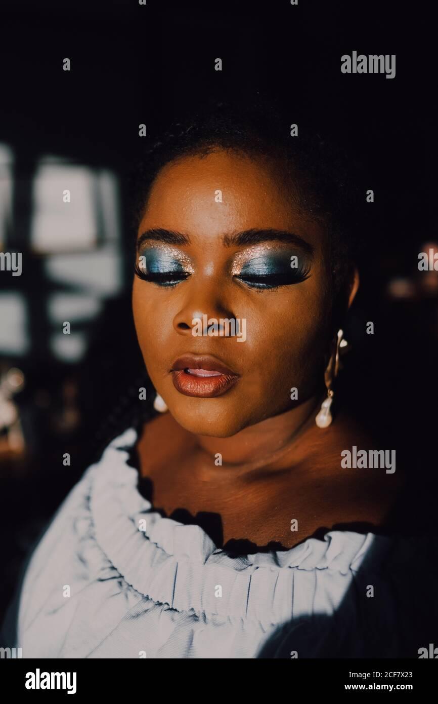 Portrait de rétro-éclairé beau curvy noir jeune femme avec lumineux maquillage dans la robe hors-épaule en regardant vers le bas Banque D'Images