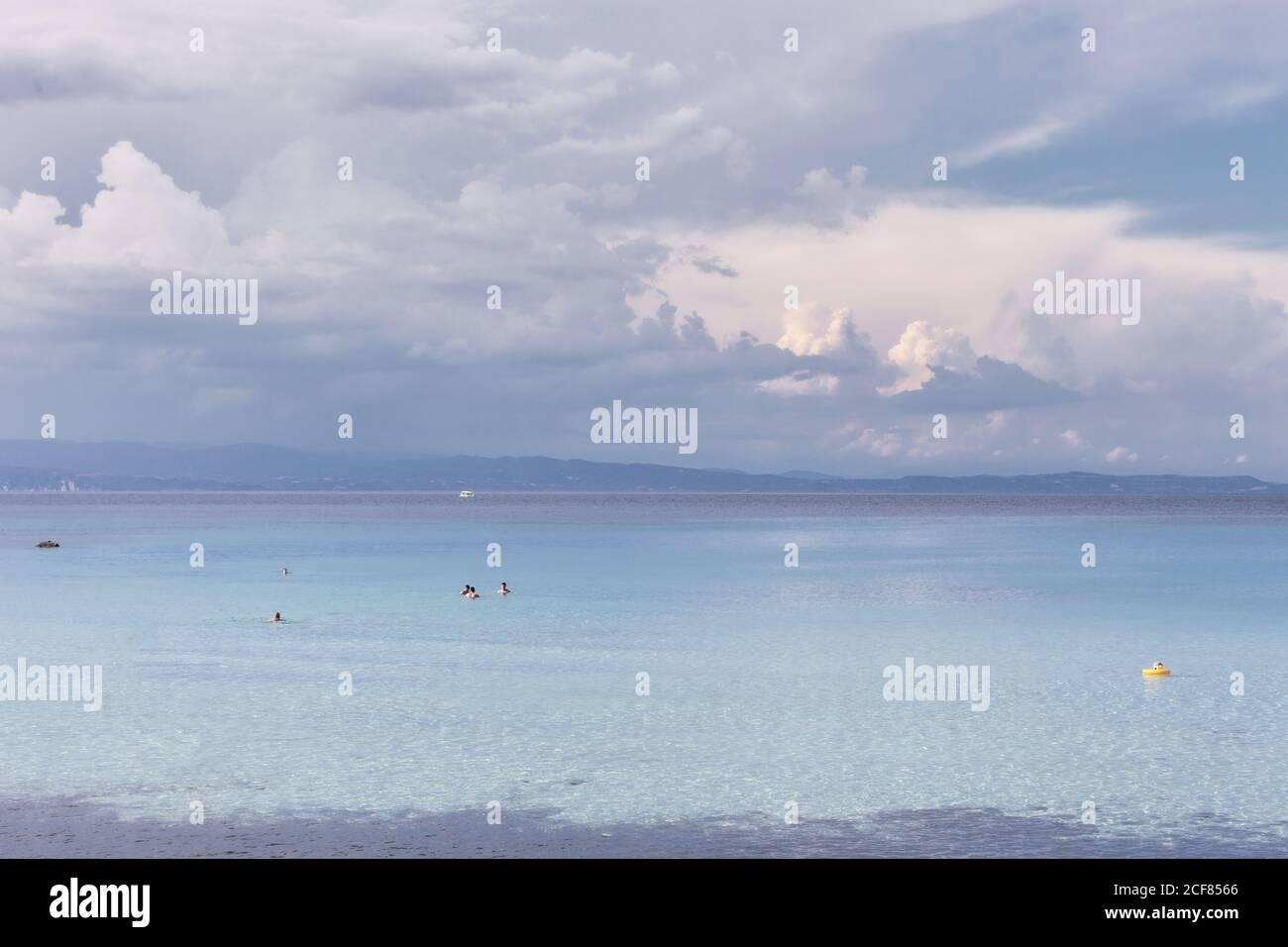 Eau de mer paisible avec des personnes nageant dans un climat calme sous ciel nuageux, Halkidiki, Grèce Banque D'Images