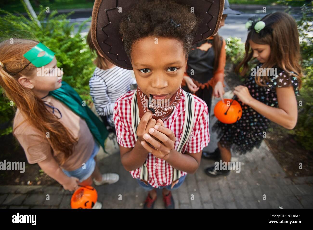 Portrait d'un garçon africain mangeant sucré et regardant l'appareil photo avec ses amis en arrière-plan à l'extérieur Banque D'Images