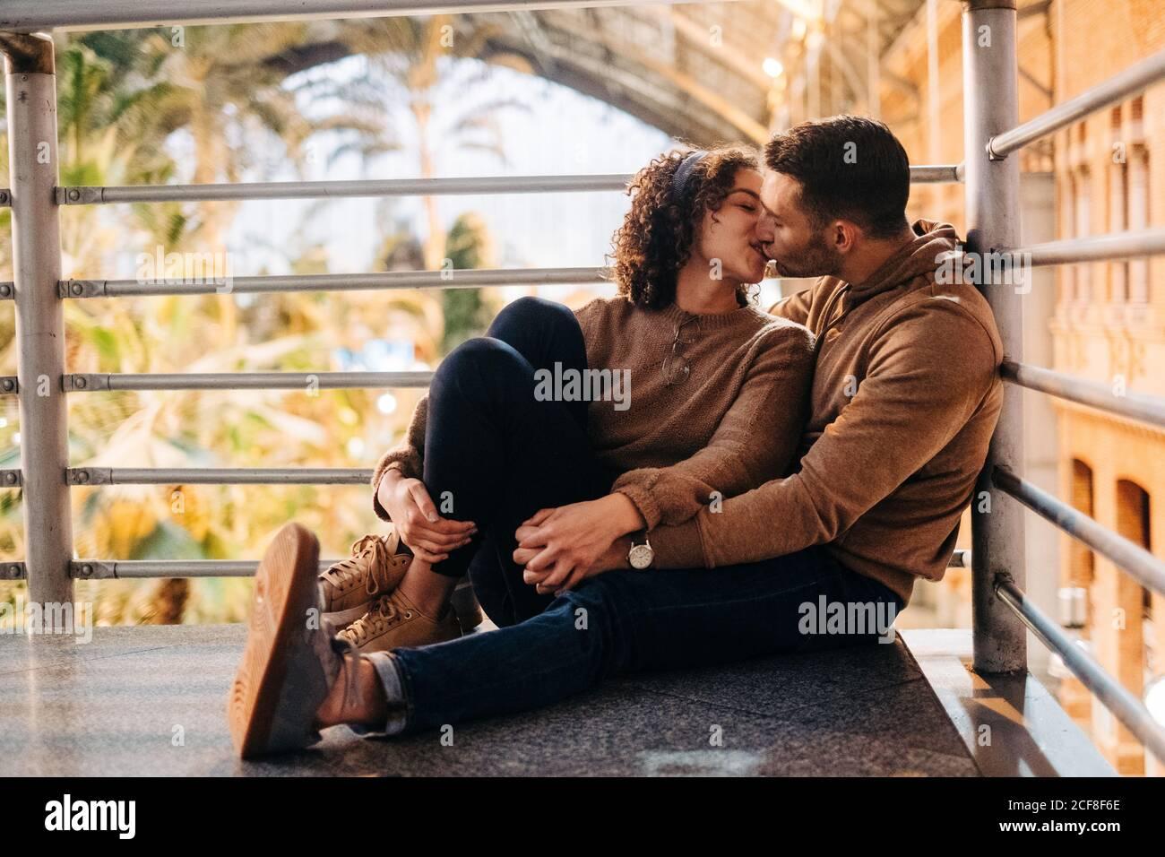 Joyeux jeune homme et femme embrassant et embrassant regarder les uns les autres en étant assis dans un pavillon éclairé pendant la date Banque D'Images