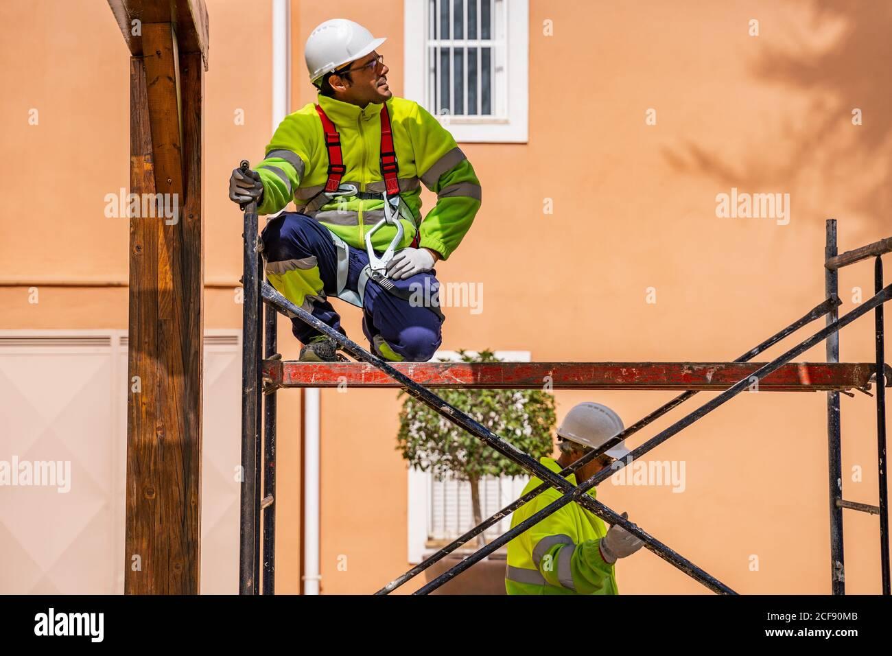 Ingénieur professionnel en uniforme et casque assis sur un échafaudage et regarder loin en travaillant avec un collègue sur l'entretien de l'électricité équipement près du bâtiment résidentiel Banque D'Images