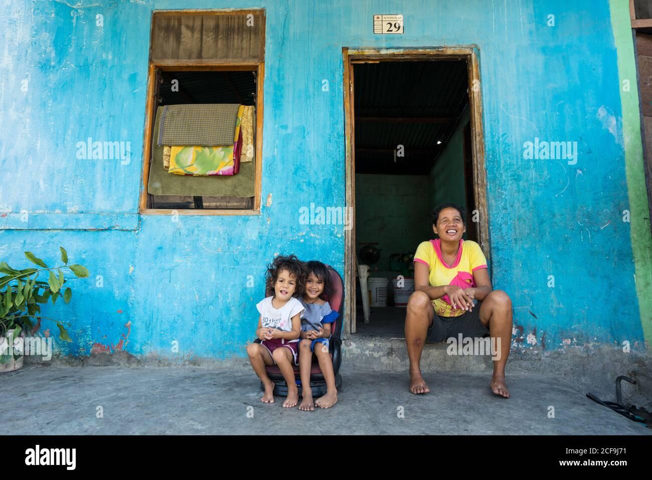 Dili, Timor oriental - 09 AOÛT 2018: Femme gaie et petites filles regardant la caméra tout en étant assis à la porte de la maison pauvre Banque D'Images