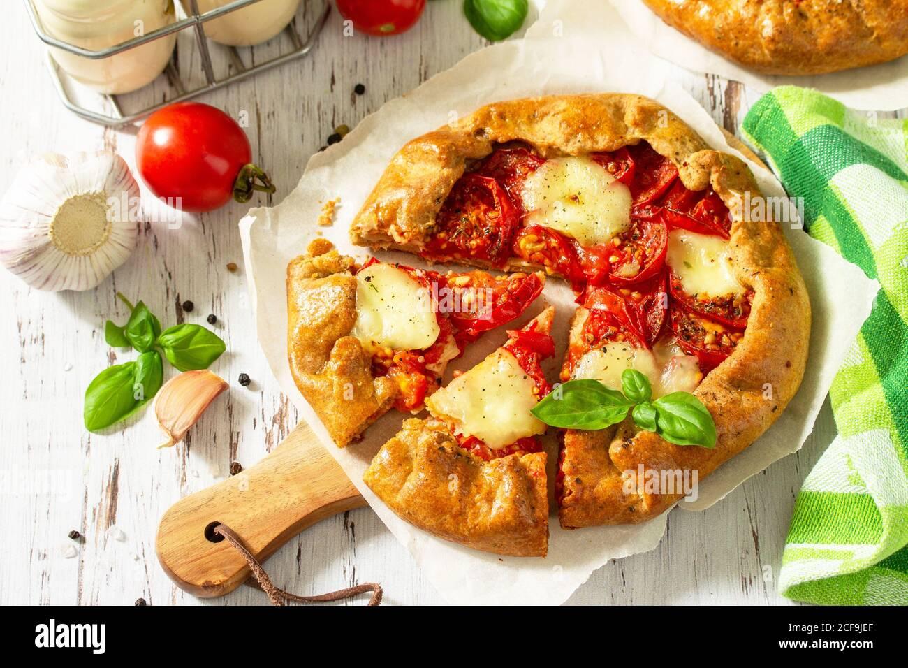 Pâtisseries saines à base de farine de seigle, aliments diététiques. Tomates Galette, mozzarella et basilic sur une table en bois. Banque D'Images