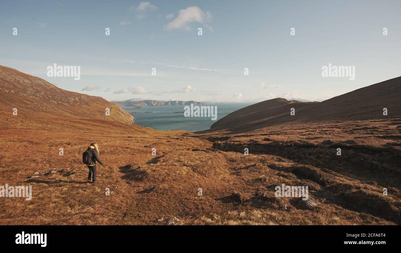 Vue arrière d'une femme méconnaissable marchant sur un paysage merveilleux Et la mer en se tenant sur la falaise en Irlande en regardant loin Banque D'Images