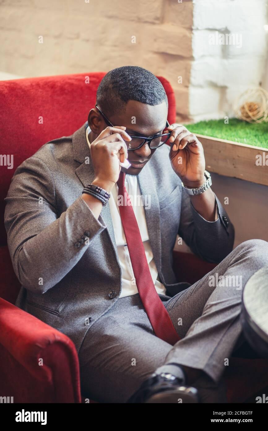 Portrait d'un jeune homme d'affaires afro-américain confiant et réussi portant des lunettes élégantes et un élégant costume sombre habillé sourire heureux, réjouissez-vous Banque D'Images
