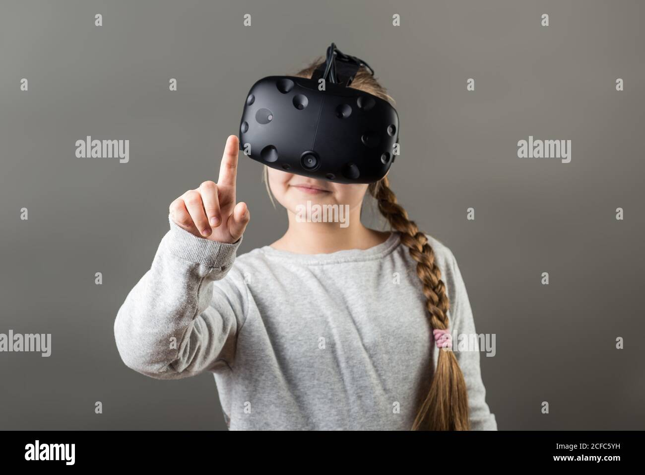 Une fille s'y porte avec un appareil VR et touche le doigt air Banque D'Images