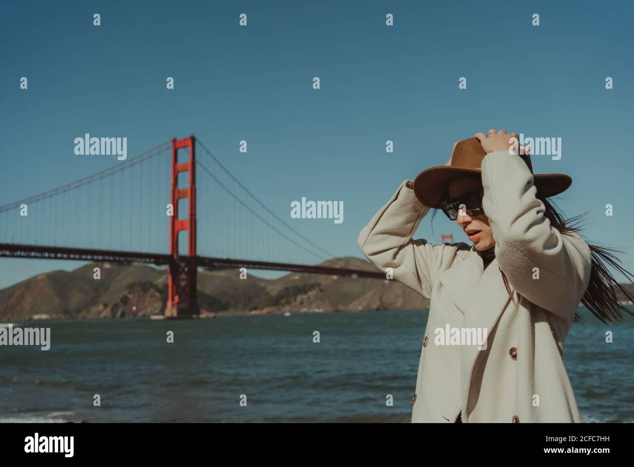 Vue latérale d'une jeune femme avec chapeau et tenue tendance Et des lunettes de soleil se tenant sur le remblai contre le pont du Golden Gate dedans Californie en journée ensoleillée Banque D'Images