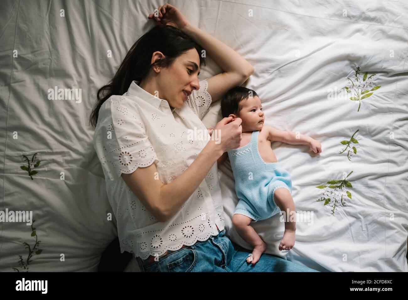 Belle femme adulte touchant doucement bébé doux tout en étant couché lit confortable Banque D'Images