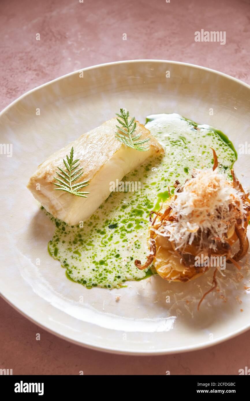 Sauce à la crème à un plat de poisson délicieux avec des herbes sur le rose expérience dans le restaurant Banque D'Images