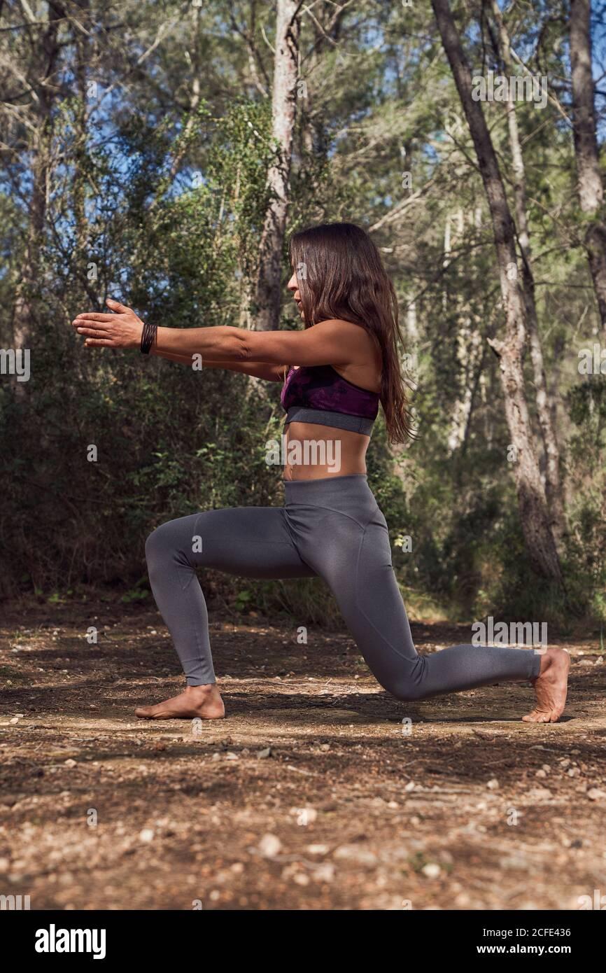 Corps complet de jeune femme en sport pratiquant la variation D'Anjaneyasana pendant le cours de yoga dans la forêt de printemps sur frais air Banque D'Images