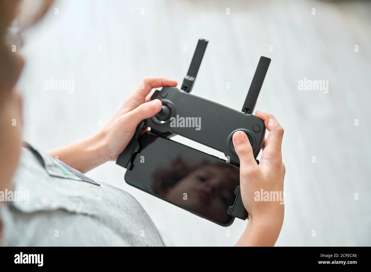 Enfant manipulant un drone et la télécommande qui vient d'être donnée à lui Banque D'Images